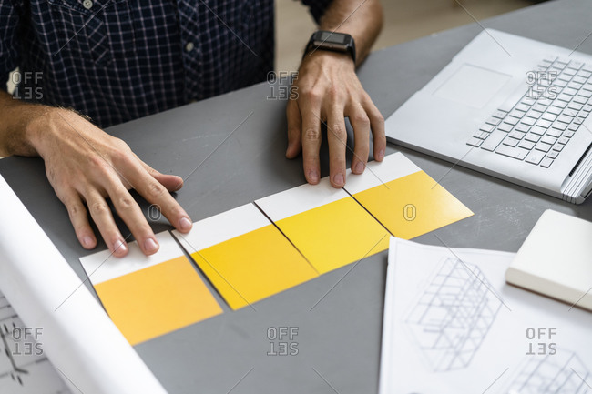 Architect choosing shade of yellow on desk at office