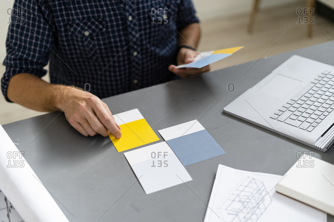 Architect choosing color swatch while sitting by desk at office