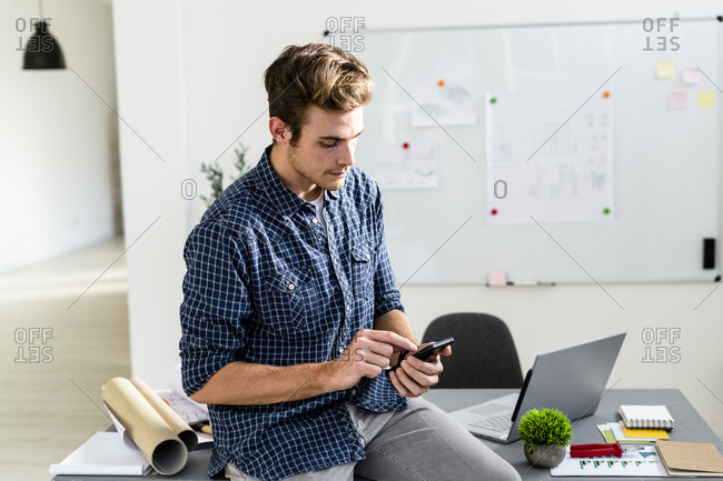 Young man using mobile phone while sitting on desk at office