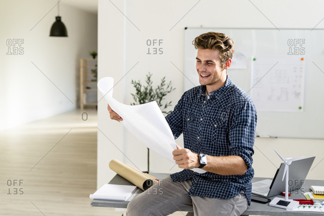 Smiling young man holding blueprint while sitting on desk at office