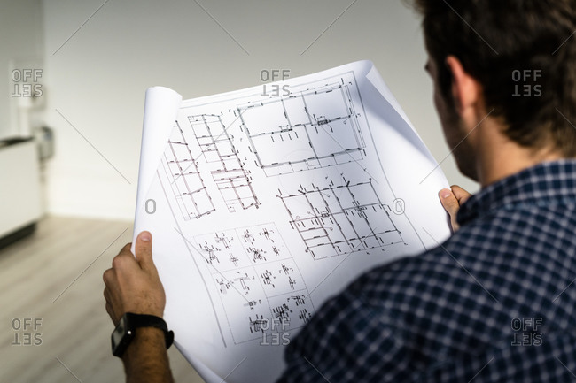 Architect reading blueprint while sitting at office