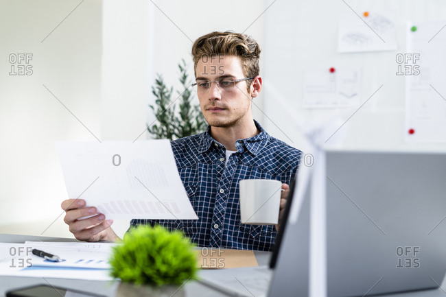 Man holding paper while drinking coffee at office
