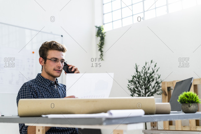 Architect discussing plan while sitting by desk at office