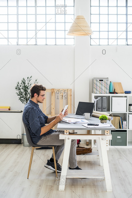 Architect working on digital tablet while sitting at office