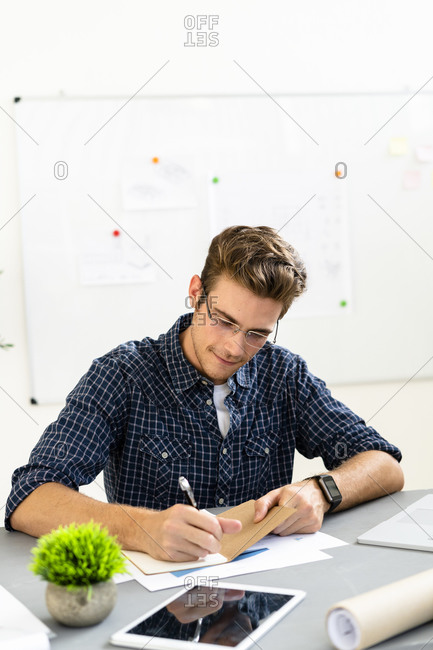 Architect writing on paper while sitting by desk at office