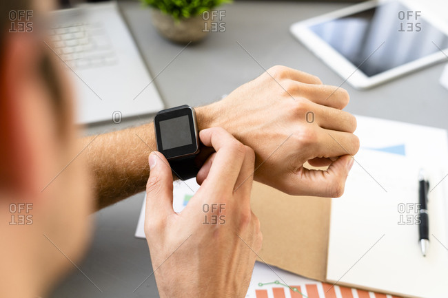 Man looking at smart watch while sitting by desk at office