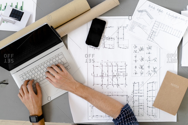 Architect working while sitting by desk at office