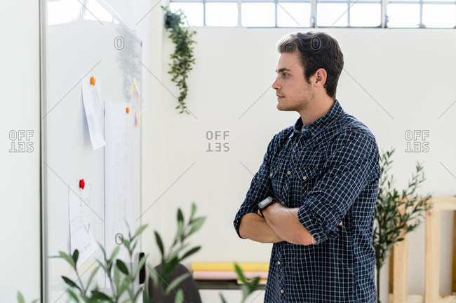 Man with arms crossed looking at whiteboard while standing in office