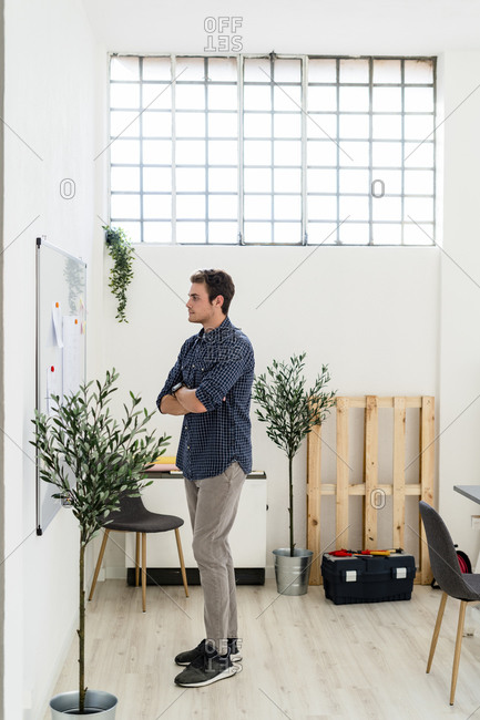 Man with arms crossed standing at office