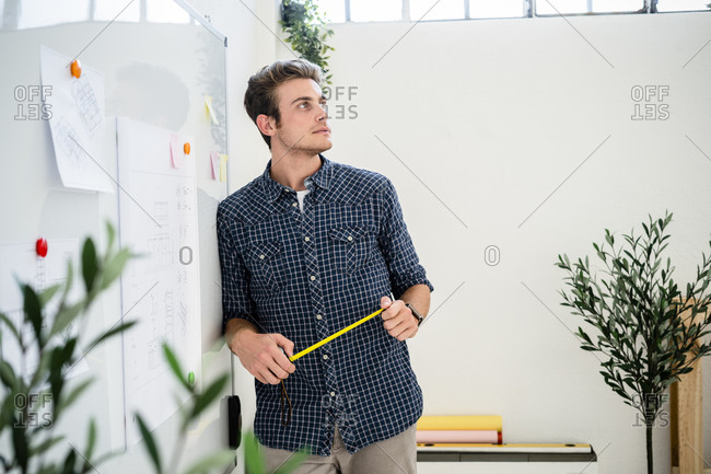 Thoughtful man leaning on whiteboard while standing at office