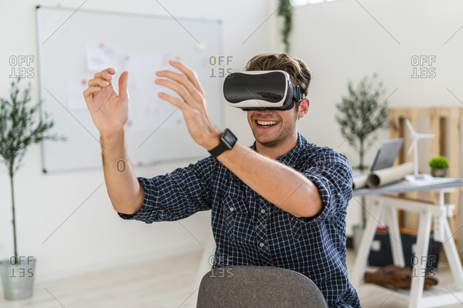 Smiling architect using visual reality simulator while sitting on chair at office
