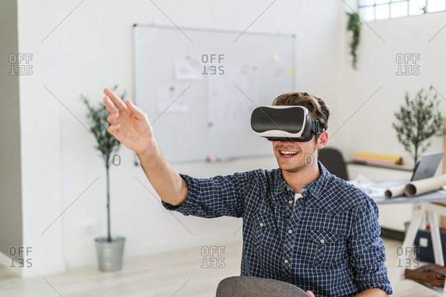 Smiling man sitting on chair while using visual reality simulator at office