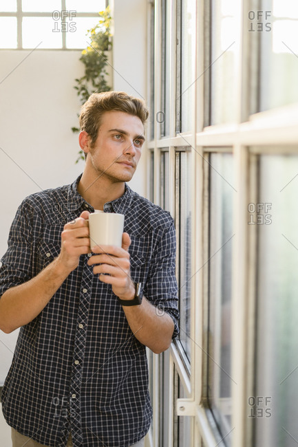 Man looking through window while standing at office