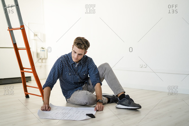 Architect sitting on floor while reading blueprint at office