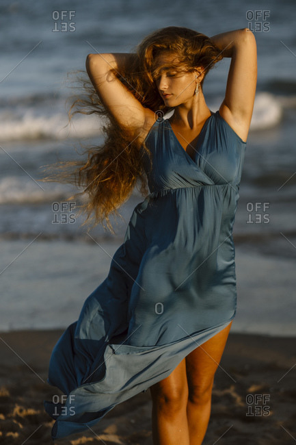 Woman standing with hands behind head at beach