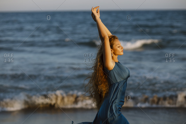 Beautiful woman with hand raised dancing while standing against sea