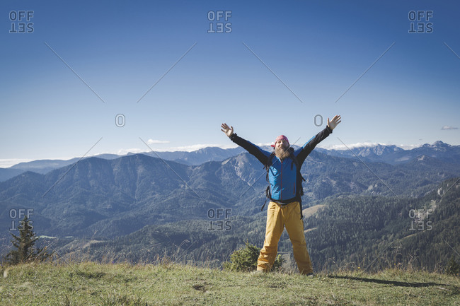 Mature man with arms raised standing on mountain against clear sky- Otscher- Austria