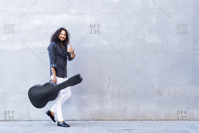 Smiling man with guitar showing thumps up while walking against gray wall