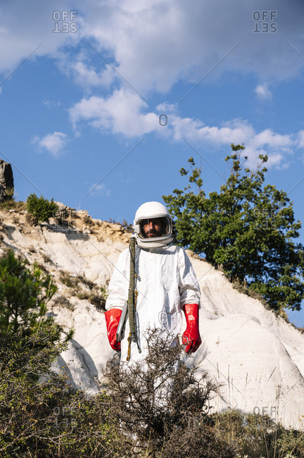 Male astronaut wearing space suit standing on mountain against sky