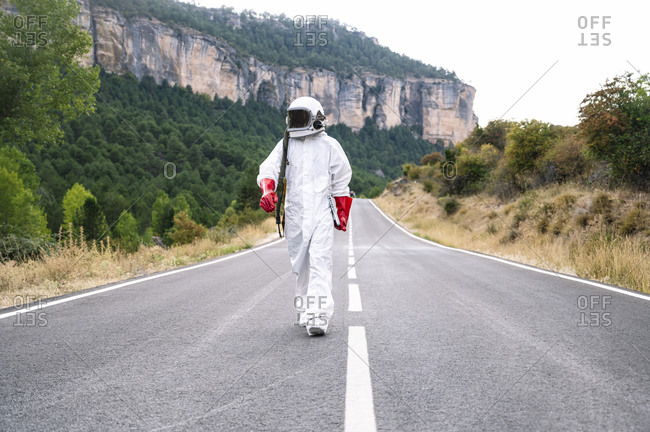 Male astronaut wearing space suit walking on road against mountain