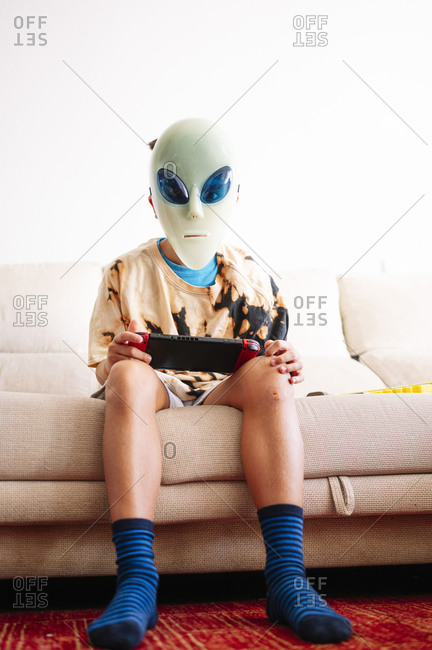 Boy wearing alien mask playing handheld video game while sitting on sofa at home