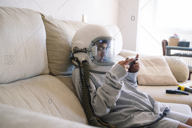 Boy wearing space helmet playing handheld video game while relaxing on sofa at home