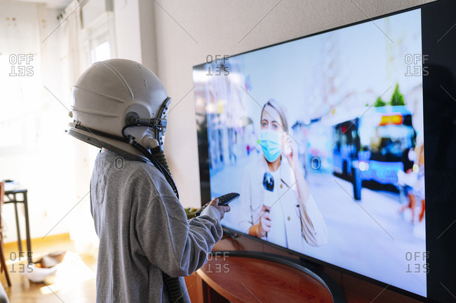 Boy wearing space helmet watching journalist mother on TV while standing at home