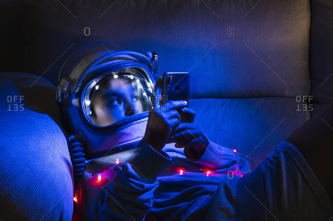 Boy wearing space helmet using mobile phone while relaxing on sofa in illuminated home