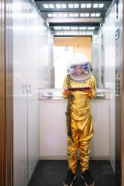 Boy wearing space suit playing video game while standing in open elevator