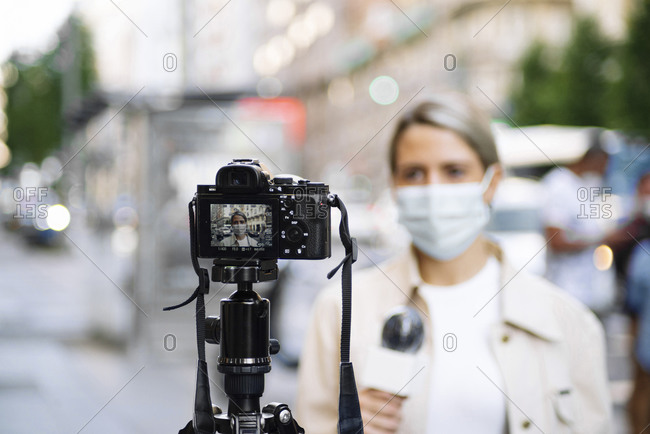 Female journalist wearing mask filming with camera in city