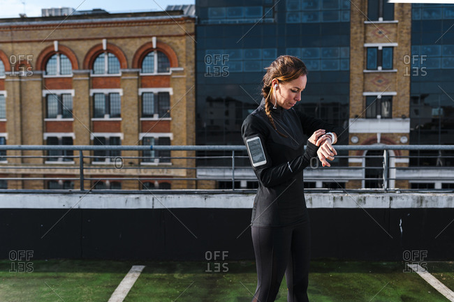 Female athlete checking smart watch while standing on rooftop in city