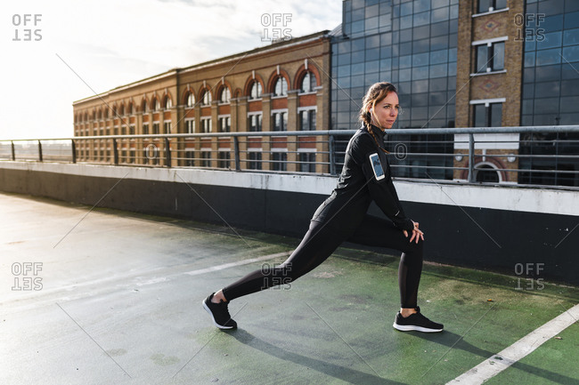 Female athlete stretching legs on rooftop against buildings in city