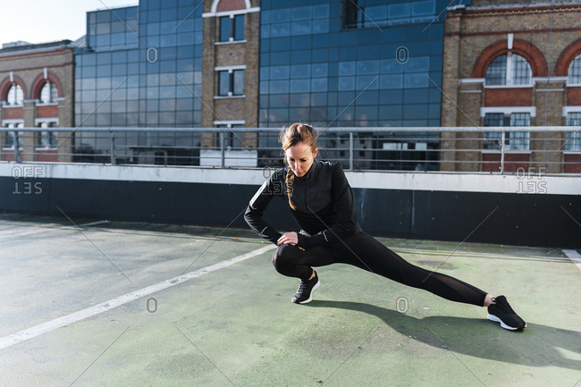 Female athlete stretching legs on rooftop against building in city