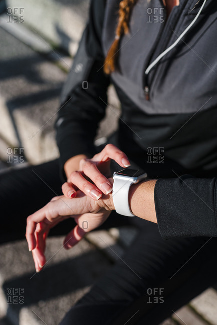 Close-up of female athlete using smart watch while sitting on steps