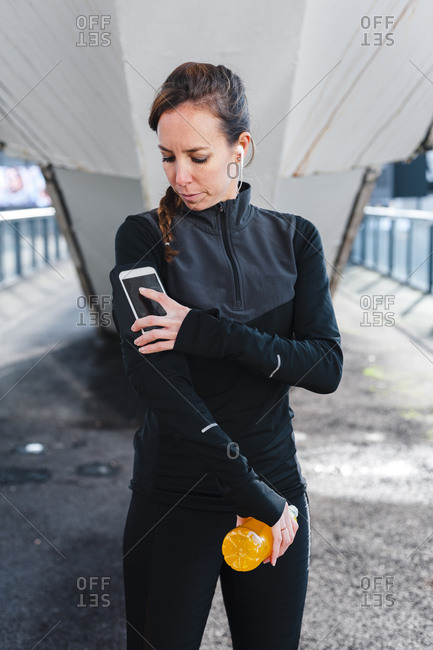 Female athlete using smart phone over arm band while standing on footpath