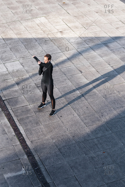 Female athlete stretching hands while standing on rooftop