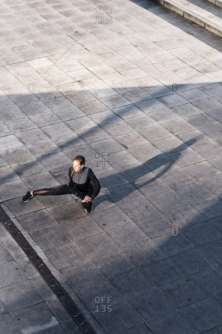 Female athlete stretching legs while crouching on rooftop