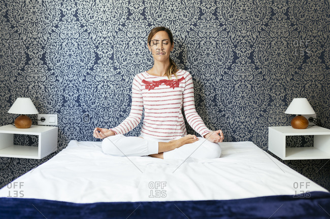 Mid adult woman meditating in lotus position on bed against patterned wall at home