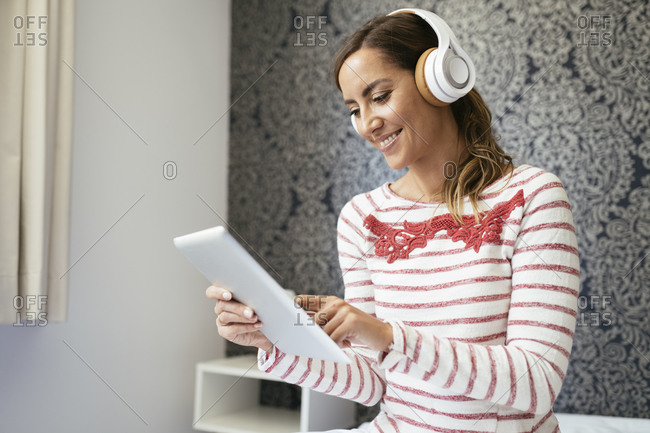 Smiling woman listening music over headphones while using digital tablet at home