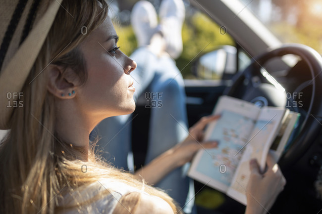 Young woman holding travel guide while sitting in car