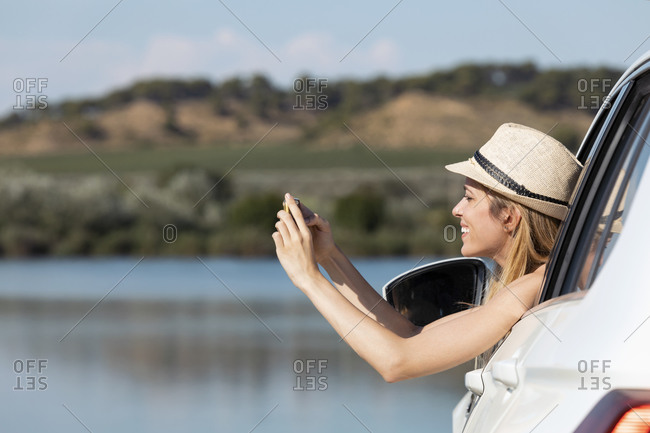 Young woman leaning on car window while taking photo with phone sitting in car