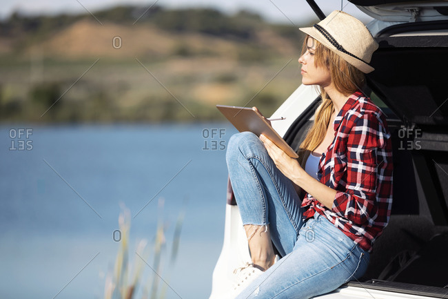 Young woman using digital tablet while sitting at car trunk