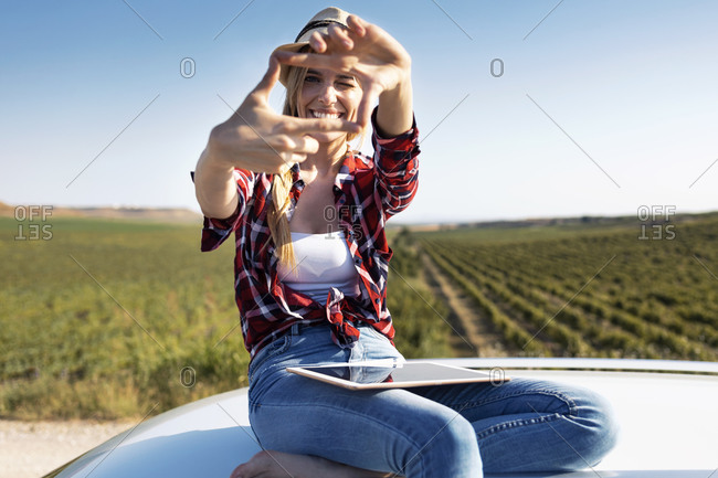 Smiling young woman showing finger frame while sitting on car roof