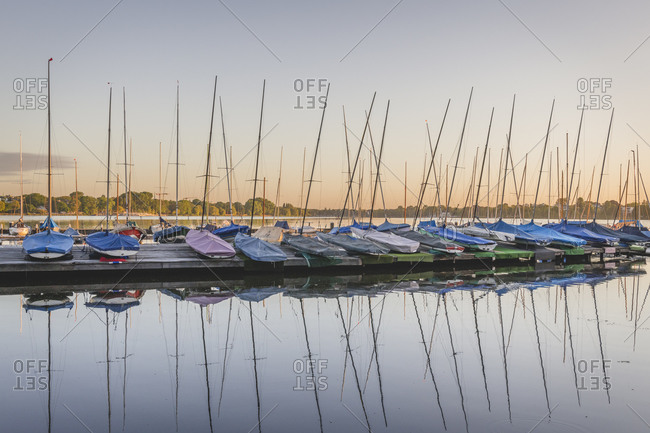 Germany- Hamburg- Row of sailboats moored on Outer Alster Lake at sunset