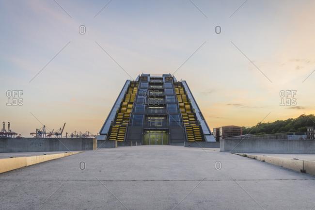 Germany- Hamburg- Illuminated modern office building near dock at sunset