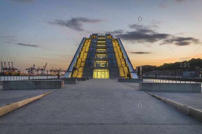 May 28, 2020: Germany- Hamburg- Illuminated modern office building near dock at sunset