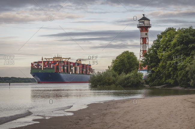 Germany- Hamburg- Container ship on Elbe river and Wittenbergen lighthouse at sunset