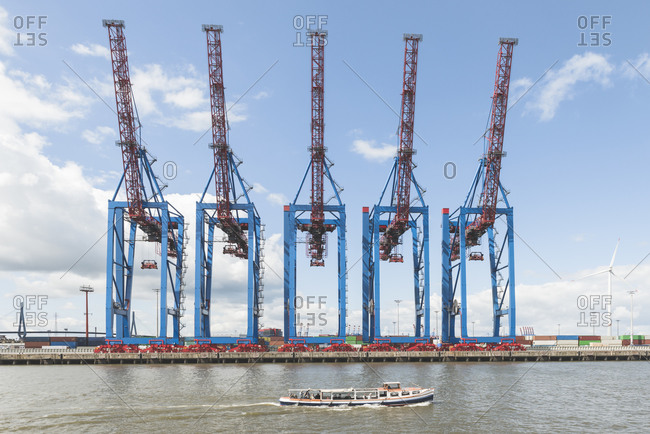 Germany- Hamburg- Barge on river Elbe with dock cranes in background