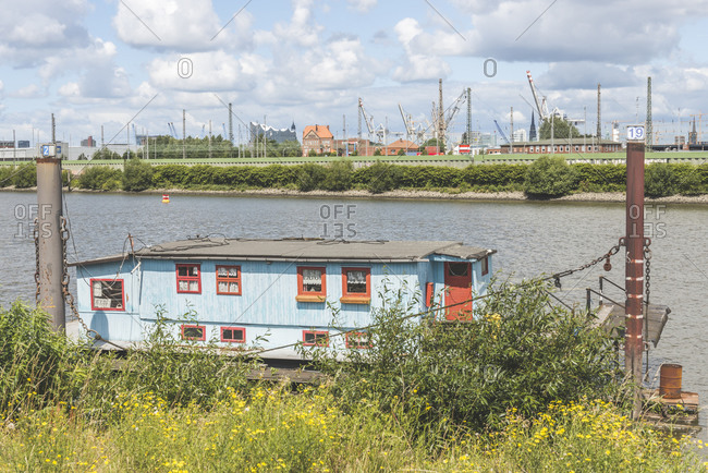 Germany- Hamburg- Spreehafen- Houseboat on river with dock in distance