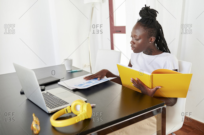 Young businesswoman analyzing reports on desk while sitting at home